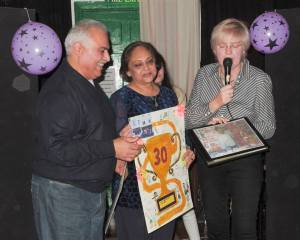 Vinod & Meena receiving cards and 'Bright News in The Whistler' book from Colette