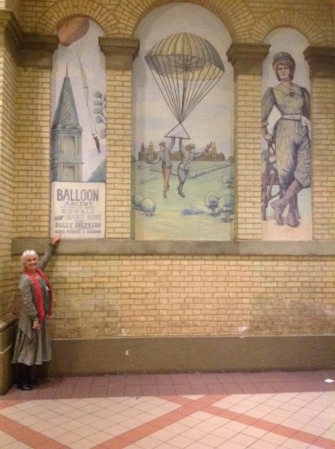 Kate at Alexandra Palace next to the murals of Dolly Shepherd